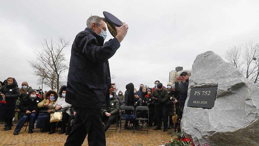 Ein Pilot legt Blumen vor der Gedenkstätte für die Opfer des Absturzes einer ukrainischen Passagiermaschine nieder. Ein Jahr nach dem Abschuss des Flugzeuges dringt Präsident Selenskyj auf den Beginn eines Gerichtsverfahrens.