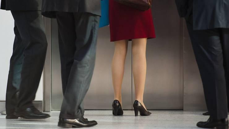 Eine Frau umringt von Männern. In der Schweiz beträgt die Frauenquote in Verwaltungsräten magere 11,3 Prozent, geht es nach dem Bundesrat, sollen daraus 30 Prozent werden. (Symbolbild)