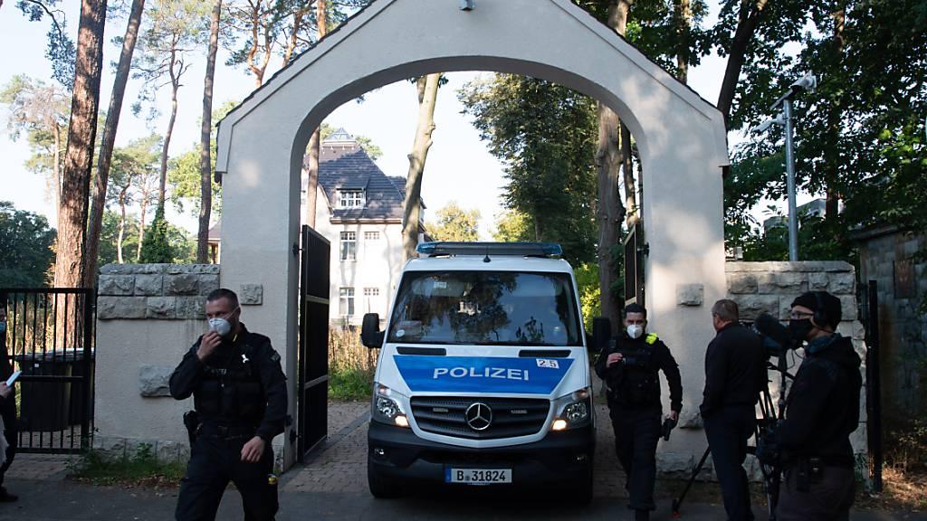 Polizeibeamte stehen im Rahmen einer Durchsuchung vor einem Grundstück in Kleinmachnow. Seit 6 Uhr morgens durchsuchen 300 Beamte der Polizei und Steuerfahndung insgesamt 18 Häuser, Wohnungen und Geschäftsräume in Berlin, Brandenburg und der Schweiz. Foto: Paul Zinken/dpa-Zentralbild/dpa