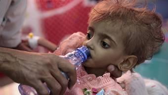 Ein Vater gibt seinem schwer unterernährten Töchterchen in einem Spital in Hodeida zu trinken. Im Hafen von Hodeida werden die meisten Importe und internationalen Hilfslieferungen für den Jemen umgeschlagen. Das Leben hunderttausender Kinder hängt davon ab. (Archivbild)