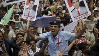 Ein Polizist im Jemen zeigt das Bild eines getöteten Demonstranten