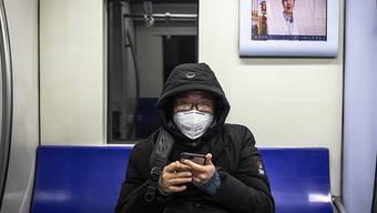 Einsam unterwegs: U-Bahn-Passagier mit Schutzmaske in Peking.