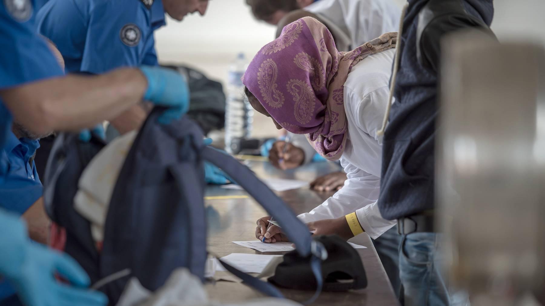 Menschen füllen bei ihrer Einreise am Bahnhof Chiasso Papiere aus. Im Moment dürfen Familien nicht mehr nach Italien zurückgeschickt werden.