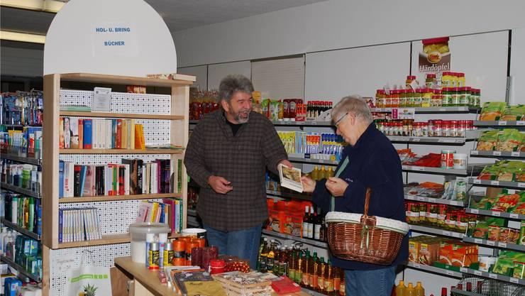 November 2012: Peter Kalt, Präsident der Ladengenossenschaft Ittenthal, mit einer Kundin dem Angebot im kleinen Dorfladen: eine Bring-und-Hol-Ecke für Bücher.