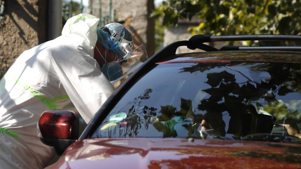 Prag: Ein junger Autofahrer wird an einer Drive-in-Teststation auf Covid-19-Symptome geprüft. In Tschechien breitet sich das Coronavirus weiter rasant aus. Foto: Petr David Josek/AP/dpa