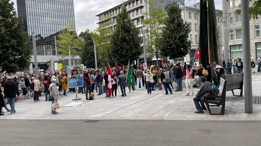 Mit Kantons- und Schweizerfahnen: Die Massnahmen-Gegnerinnen und -Gegner bei der Besammlung auf dem Kornhausplatz in St. Gallen.