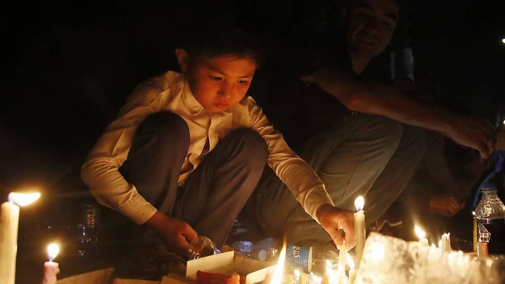 Trauer in Kabul: Ein afghanischer Bub zündet eine Kerze an in Gedenken an die mindestens 80 Todesopfer, die bei einem Selbstmordanschlag auf eine Demonstration in Kabul starben.