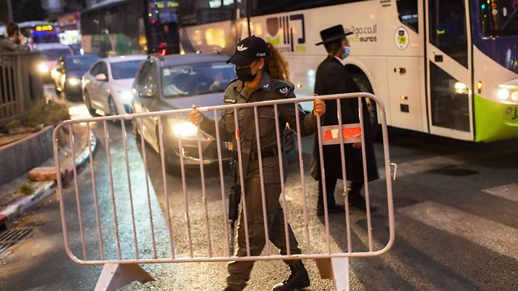 dpatopbilder - Die israelische Grenzpolizei errichtet in der ultra-orthodoxen jüdischen Stadt Bnei Brak vor einer nächtlichen Ausgangssperre auf einer Hauptstraße eine Absperrung. Israel hat die Maßnahmen für 40 israelische Städte und Ortschaften mit besorgniserregenden Corona-Fallzahlen verschärft. Foto: Oded Balilty/AP/dpa