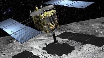 Hayabusa2 beim Sammeln von Gesteinsproben auf dem Asteroiden Ryugu. Die Arbeit ist getan, am Samstag wirft Hayabusa ihr Sammelkörbchen im Vorbeifliegen an der Erde ab, um gleich wieder zur nächsten Mission weiter zu ziehen. (JAXA)
