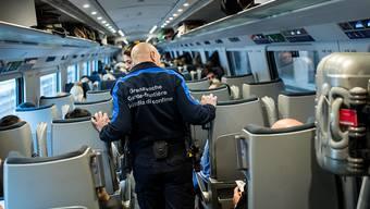 Mitarbeiter der Grenzwache kontrollieren in einem Zug Passagiere. (Archivbild)