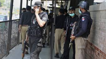 Polizeibeamte stehen nach der Ermordung von Tahir Shamim Ahmad, der vor Gericht der Beleidigung des Islam beschuldigt wurde, an einem Eingangstor des Bezirksgerichts im Nordwesten Pakistans. Foto: Muhammad Sajjad/AP/dpa