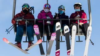 Skifahrer auf einer Sesselbahn im Skigebiet Verbier.
