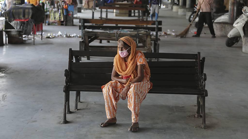 Eine Frau trägt eine Schutzmaske und wartet an einem verlassenen Busbahnhof. (Archivbild)