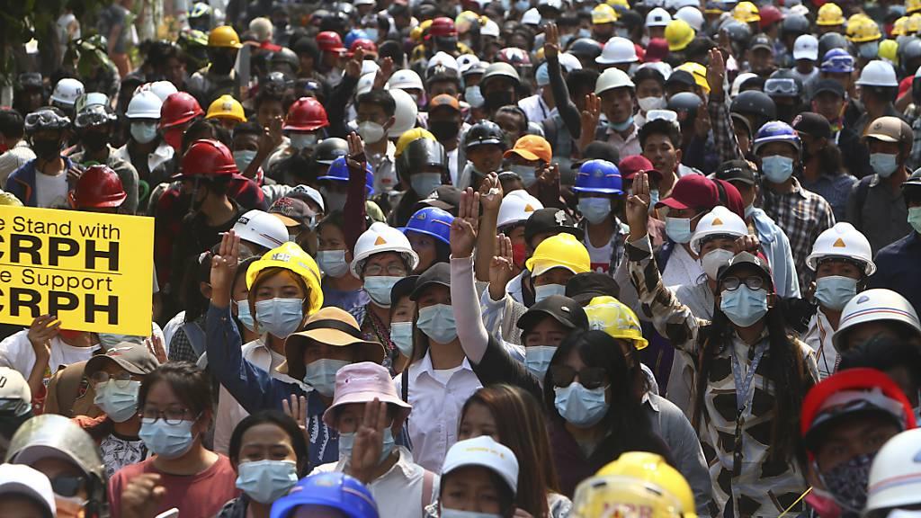 Demonstranten zeigen bei einem Protest gegen den Militärputsch den Dreifingergruß. Trotz Polizeigewalt haben in Myanmar am Samstag erneut landesweit Hunderttausende Menschen gegen die Militärjunta protestiert. Foto: Str/AP/dpa