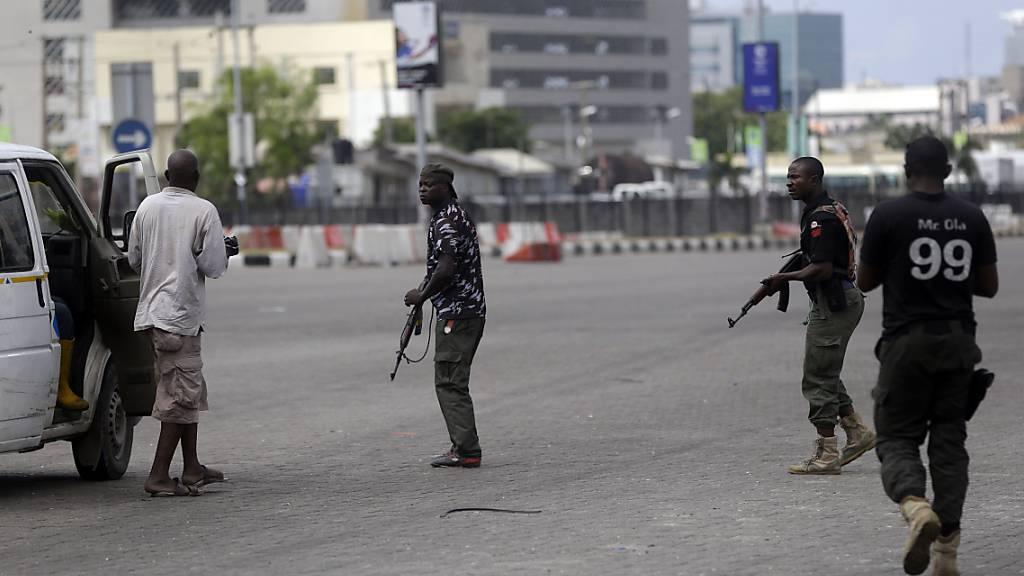 Polizisten kontrollieren einen Mini-Bus auf der Straße. Foto: Sunday Alamba/AP/dpa