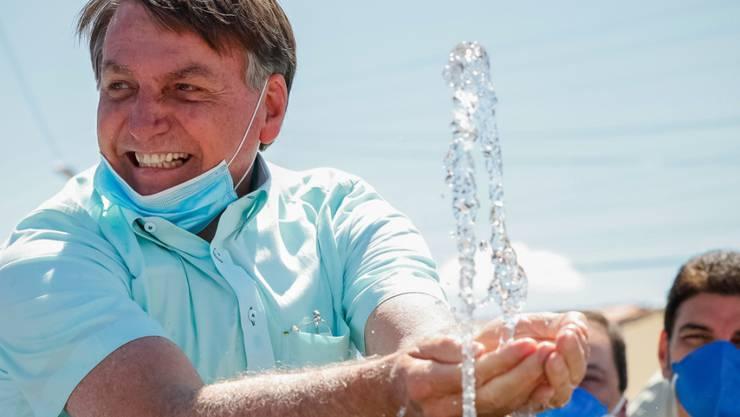 HANDOUT - Auf diesem vom brasilianischen Präsidentenamt zur Verfügung gestellten Bild lächelt Jair Bolsonaro, Präsident von Brasilien, mit untergezogenem Mundschutz, während er an einem Brunnen zur lokalen Wasserversorgung mit Wasser spielt. Foto: Alan Santos/Palacio Planalto/dpa