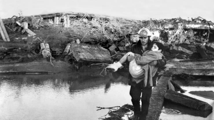 Ein Feuerwehrmann bringt einen kleinen Jungen in Sicherheit, nachdem das Wohnhaus seiner Familie zusammenstürzte.