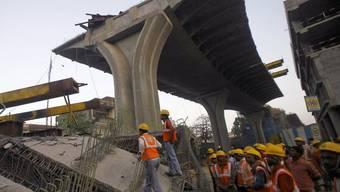 Bauarbeiter stehen neben der eingestürzten Brücke in Mumbai