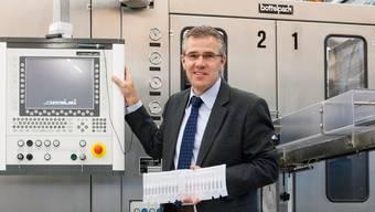 Geschäftsführer Ernst Schweizer vor einem neuen Automaten, in der Hand hält er ein Band mit Ampullen.