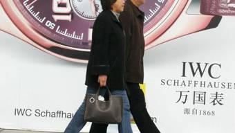 Chinesen vor Plakat einer Schweizer Uhrenmarke (Symbolbild)