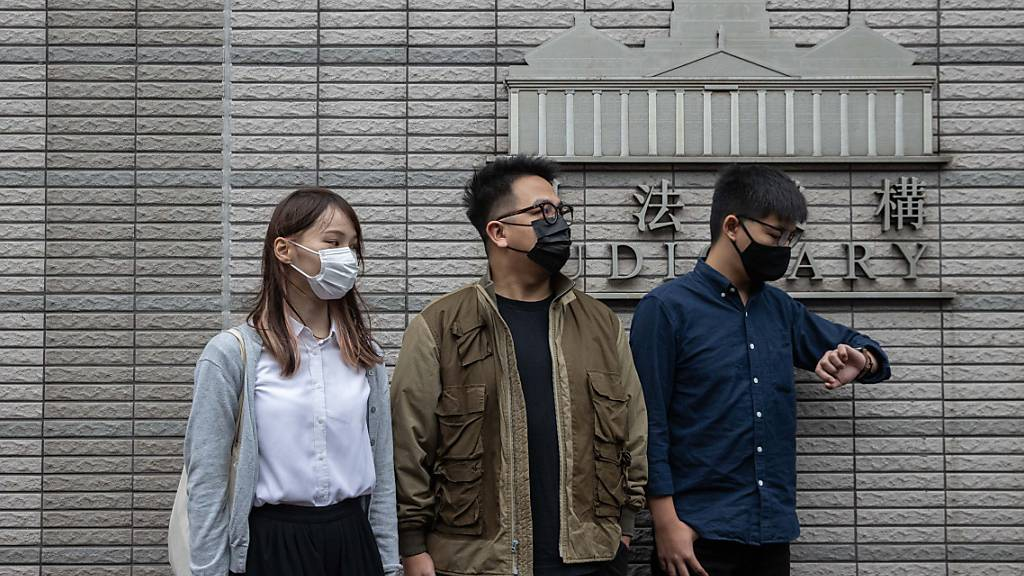 Die drei Demokratie-Aktivsten  Agnes Chow Ting (links), Ivan Lam Long Ying (Mitte) and Joshua Wong Chi-fung (rechts) vor dem West Kowloon Law Courts building in Hong Kong. Alle drei wollen sich vor dem Gericht schuldig bekennen.