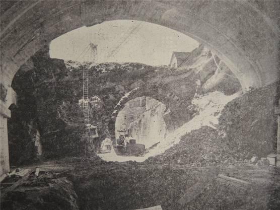Imposante Ansicht der letzten Bauphase des Schlossberg-Strassentunnels. Ausserhalb des frisch betonierten Gewölbes erkennt man den alten Tunnelausgang des Eisenbahntunnels.