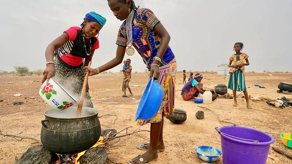 HANDOUT - Frauen bereiten im Norden des Landes auf einem offenen Feuer in einem großen Topf eine Mahlzeit zu. Foto: Giles Clarke/UNOCHA/dpa - ACHTUNG: Nur zur redaktionellen Verwendung und nur mit vollständiger Nennung des vorstehenden Credits