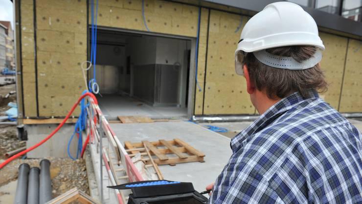 Ein Arbeitskontrolleur prüft die Bedingungen auf einer Baustelle. (Archiv)