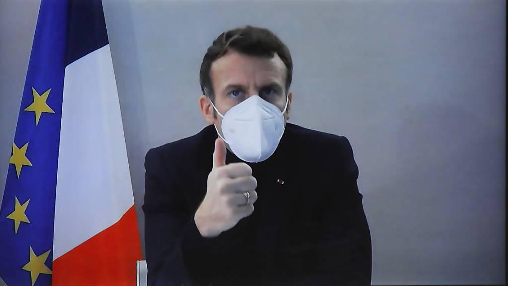 Emmanuel Macron, Präsident von Frankreich, ist während seiner Teilnahme an einer digitalen Nationalen Humanitären Konferenz auf einem Bildschirm eingeblendet, und hält den Daumen hoch.