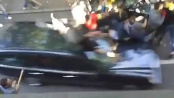 Ein Automobilist fährt in eine Gruppe von Menschen.