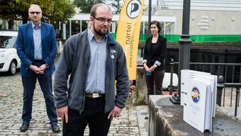 Stefan Ott, Präsident der Piratenpartei Aargau (im Vordergrund) hat Urs Meier und Franziska Gross von der Staatskanzlei die Unterschriften übergeben.