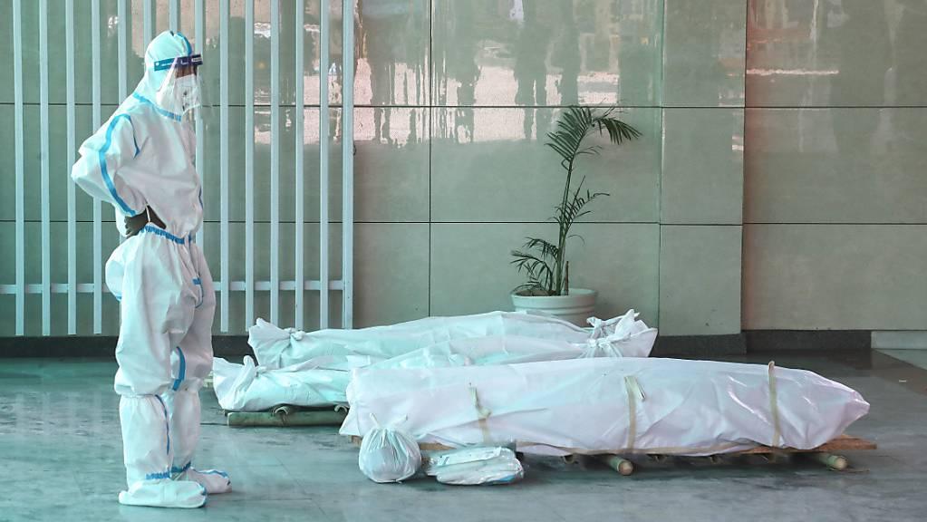 Ein Angehöriger steht in einem indischen Krematorium vor dem Leichnam eines verstorbenen Corona-Patienten.