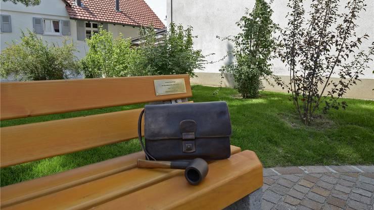 Die Bank mit Symbolen, die typisch sind für Otto Stich: Eine Pfeife und eine Tasche aus Bronze.