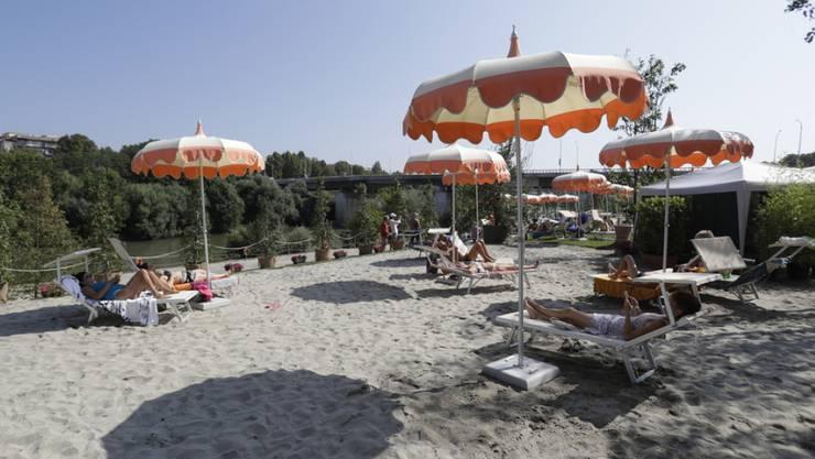 Sonnenbadende am ersten Sandstrand am Tiber in Rom.