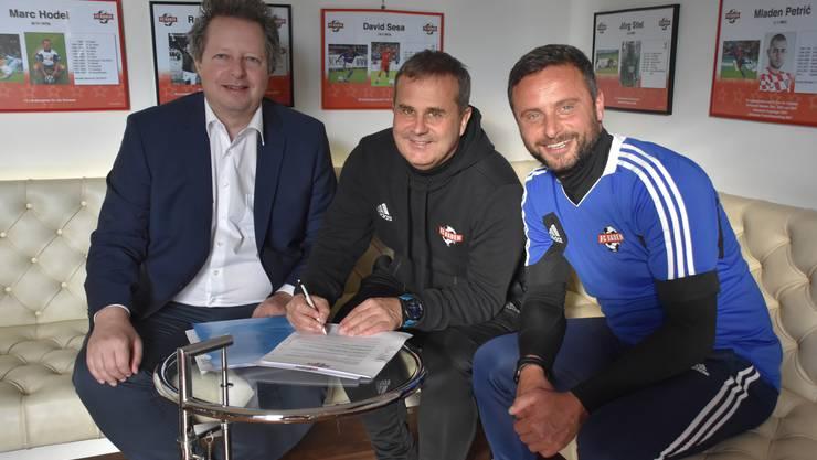 Thomi Bräm, Präsident des FC Baden, unterschreibt zusammen mit Trainer Thomas Jent und Assistenztrainer Rino Luongo die Verträge für kommende Saison.