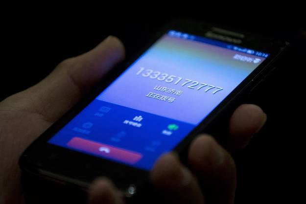 Ein chinesischer Mann zeigt Journalisten sein Handy. Er behauptet, er rufe einen der Passagiere von Flug MH370 an - es klingelt, aber niemand nimmt ab.