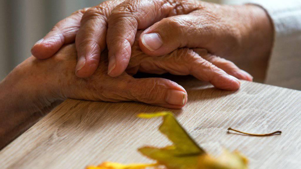 Zwei Bewohnerinnen in einer Wohngemeinschaft für Demenzkranke halten sich die Hände - die Zahl der Demenzkranken werde voraussichtlich von derzeit knapp 50 Millionen bis zum Jahr 2050 auf 152 Millionen wachsen, sagt die WHO.