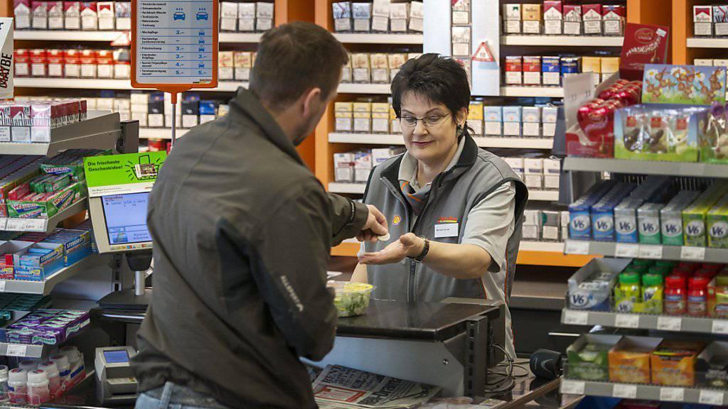 Eine Mitarbeiterin in einem Tankstellenshop in Stans NW bedient einen Kunden (Archivbild).