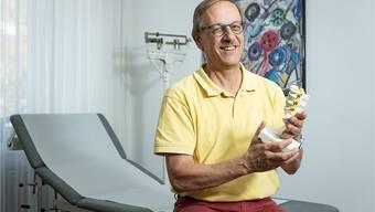 Ruedi Bosshardt zeigt ein Modell eines Lendenwirbels. Als Hausarzt behandelt er mehr als physische Gebrechen.
