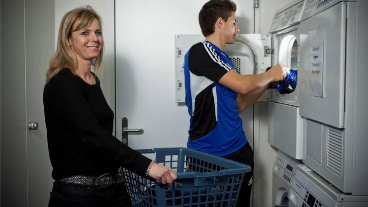 Es fällt viel Wäsche an: Internatsleiterin Karin Hug unterstützt Spieler Genc Krasniqi in der Waschküche.Chris iseli