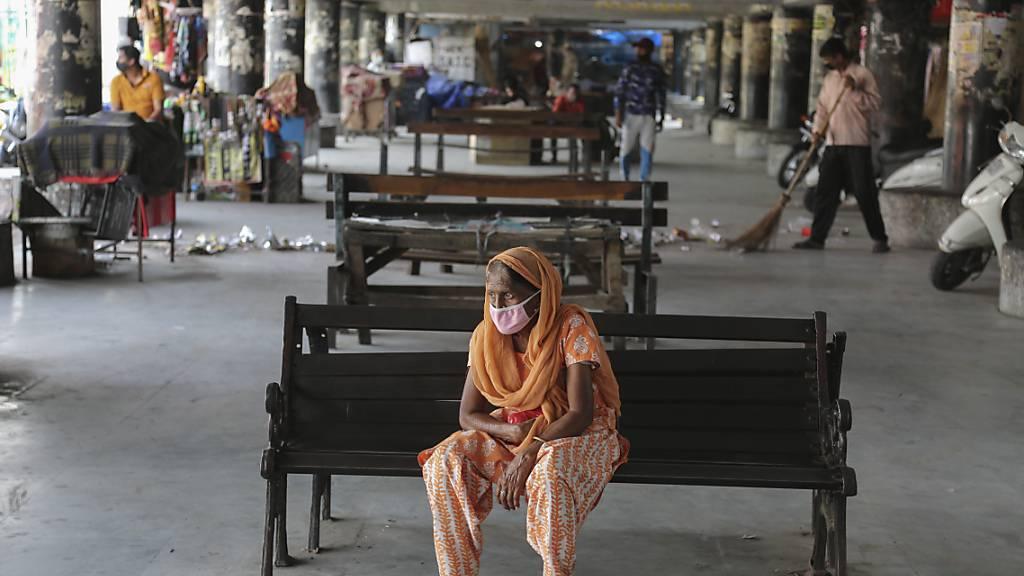 Eine Frau trägt eine Schutzmaske und wartet an einem verlassenen Busbahnhof. (Archivbild) Foto: Channi Anand/AP/dpa