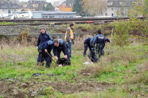 Polizisten bergen den vergrabenen Kadaver.