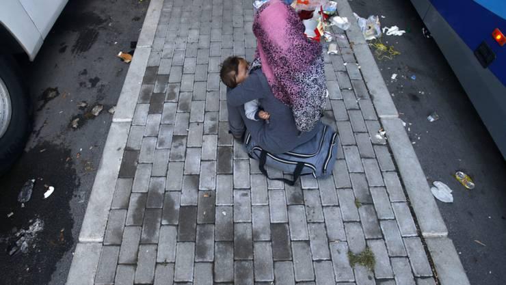 Eine Flüchtlingsfrau sitzt mit Kind auf einem Perron der Busstation in Gevgelija.