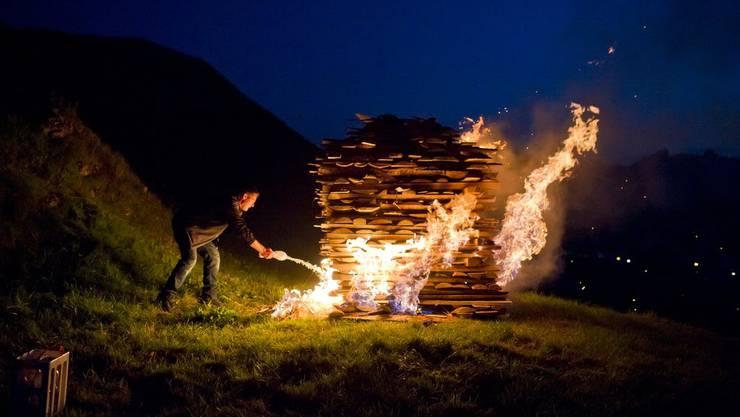 Ein Mann entzündet das Höhenfeuer in Urnäsch.