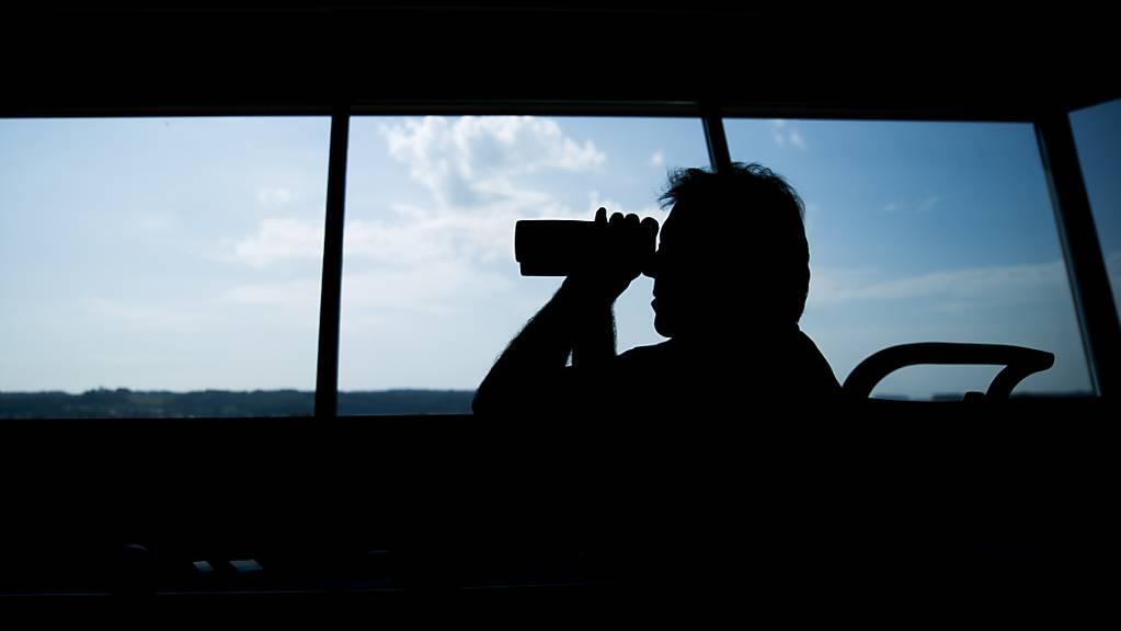 Ein Fluglotse blickt mit einem Fernglas aus dem Tower eines Flughafens. (Symbolbild)