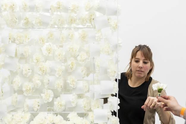 """Die Meisterfloristin mit ihrer Interpretation zu """"Ohne Titel"""" (1998) von Andreas Christen. In einem aufwendig hergestellten Rahmen hängen 300 Nelken."""