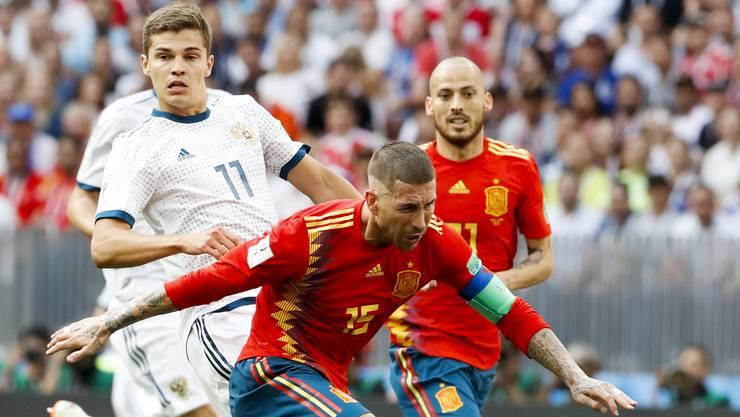 Sergio Ramos (vorne) ist einen Schritt vor Russlands Roman Zobnin am Ball. David Silva im Hintergrund beobachtet den Zweikampf.