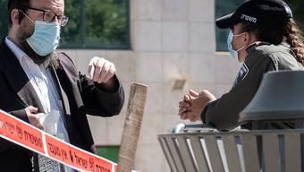 Eine Polizistin prüft den Ausweis eines jüdischen Anwohners in Jerusalem. Die israelische Regierung führt erneut Lockdown-Maßnahmen ein. Foto: Nir Alon/ZUMA Wire/dpa