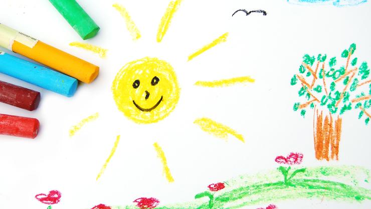 Zeichnung eines Kindes von einem Feld mit Blumen und einem Baum mit einem sonnigen Himmel. Auf der Zeichnung liegen die Ölfarbstifte.