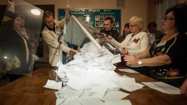 Helfer leeren in Donezk eine Urne mit Stimmzetteln